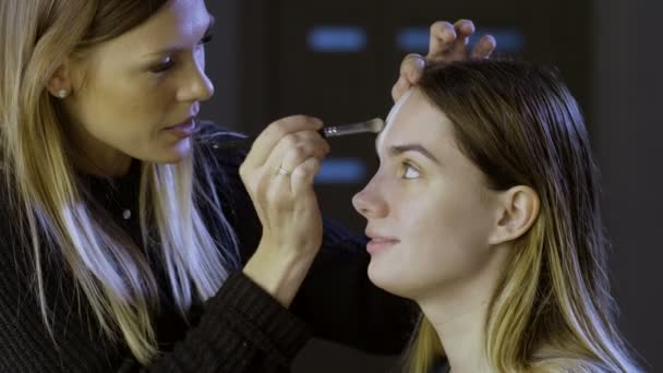 The make-up artist applying a paint on a women face and doing scary makeup for halloween in the studio. 4K