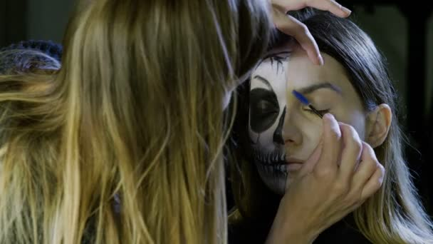 Make-up artist is making blonde woman up as dead bride for halloween party. 4K