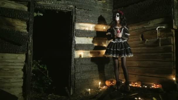 Die mexikanischen Tag der Toten. Die junge Frau mit gruselig Skelett Halloween Make-up mit einer brennenden Kerze. HD