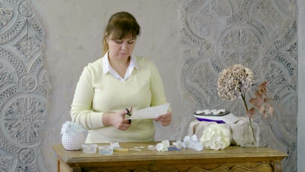 The woman making artificial hydrangeas flowers of white and beige paper. 4K
