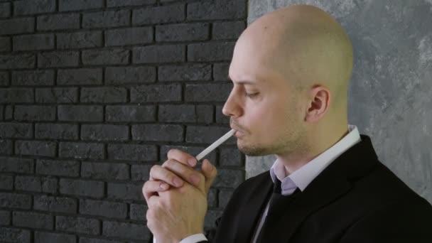Zár-megjelöl szemcsésedik-ból jóképű férfi egy fekete ruha, világítás és gőzölő egy cigaretta. 4k