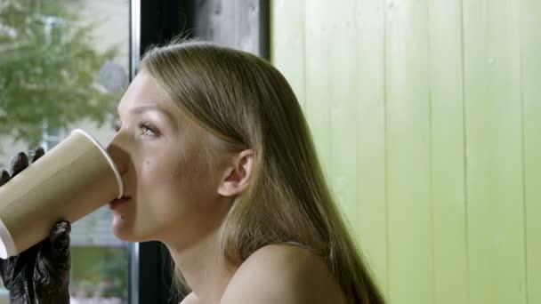 Mladá šťastná krásná žena popíjel kávu a jíst chutný hamburger v módní kavárně. 4k