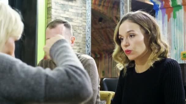 Šokovaný muž a žena, poslouchal příběh svého přítele na večeři v kavárně. 4k