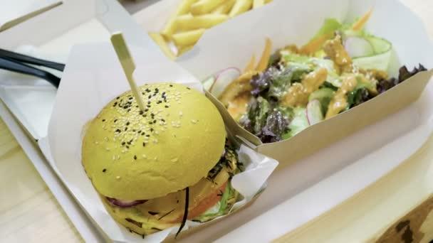 Burger. Close-up shot žluté hamburger s krevetami, hranolky, čerstvý salát. 4k