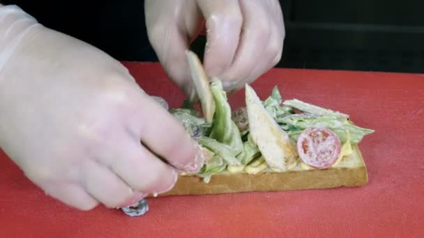 Cook cooking an open sandwich with wheat bread, chicken meat, iceberg lettuce, vegetables and egg. 4K