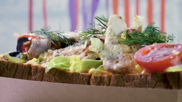 Close-up shot of an open sandwich with wheat bread, chicken meat, iceberg lettuce, vegetables and egg. 4K