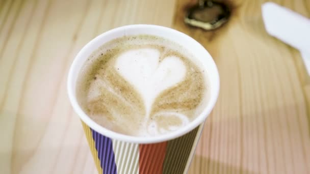 Close-up shot of milk foam in shape of heart on the top of latte or cappuccino coffee in take away cup. 4K