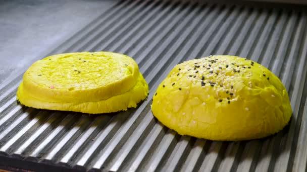 Žlutý chleba. Close-up shot ze dvou polovin hamburger buchty jsou jsou smažené na pánvi brojlerů hamburger. 4k