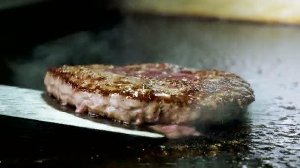 Vaření hamburger. Detailní záběr šéfkuchař převrácení hovězí nebo vepřovou kotletu grilování na roštu. 4k