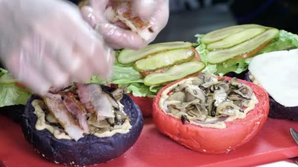 Vaření hamburger. Detailní záběr kuchař připravuje chutné burger s hovězím masem nebo vepřovou kotletu, uzenou slaninou a garnátů/krevet. 4k