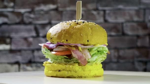 Cooking hamburger. Close-up shot of tasty burger of yellow bread, smoked bacon and fried egg. 4K