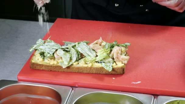 Il cuoco cucina un panino aperto con pane di grano, gamberi alla griglia, lattuga, pomodori e formaggio. 4k