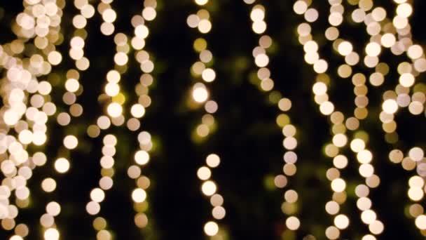 Winterurlaub. Blinkende verschwommene Weihnachtsbaumlichter bokeh auf dem Hintergrund. 4k