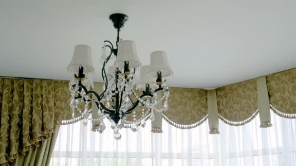 Crystal lamp. Vintage elegant chandelier on ceiling in a luxury living room. 4K