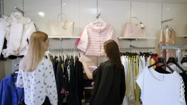 Two happy young girls are choosing clothes in a department store. 4K