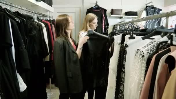 Dvě mladé dívky si oblečení v obchodním domě. 4k