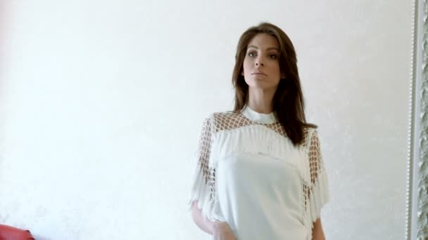 Fiatal gyönyörű barna nő megpróbálja a fehér ruha, egy ruha bolt. 4k