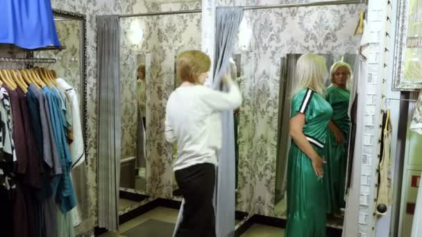 Fashion and clothing. Mid-adult attractive blonde woman trying on summer dress in a dress shop. 4K
