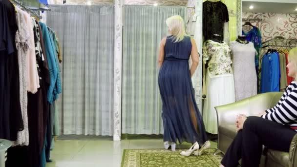 Poloviny dospělého blond žena se snaží na oblečení, boty, Dámské čepice v obchodě s oblečením. 4k