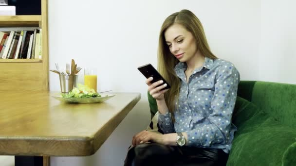 Atraktivní mladá šťastná žena pomocí mobilního telefonu během odpočinku v kavárně. 4k
