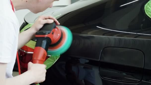 A man is polishing the black car with polisher at a car workshop. 4K