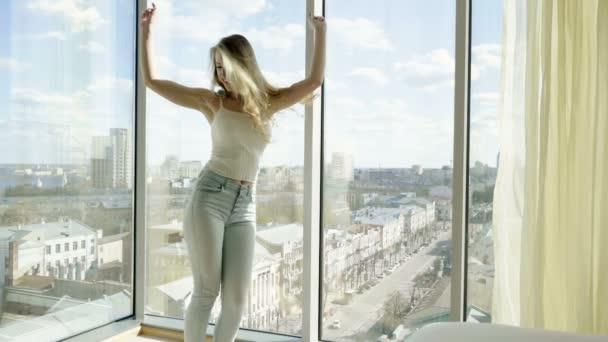 Mladá krásná blonďatá žena tančí moderní tanec před panoramatickým oknem v luxusním hotelu. Zpomaleně. Hd