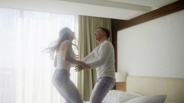 Boldog pár jumping és a szórakozás, az ágyban, a luxus hálószoba. Lassú mozgás. HD