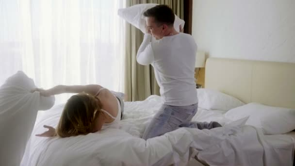 Young man and woman in love having fun and fighting with pillows in the bed at luxury bedroom. Slow motion. HD
