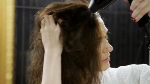 Attractive young woman dressed in bathrobe drying dark long hair with a hair dryer in bathroom at home. Slow motion. HD