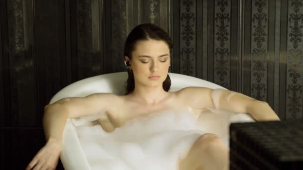 The young beautiful woman listening to music with headphones in bathtub, taking a bubble bath in luxury bathroom. 4K