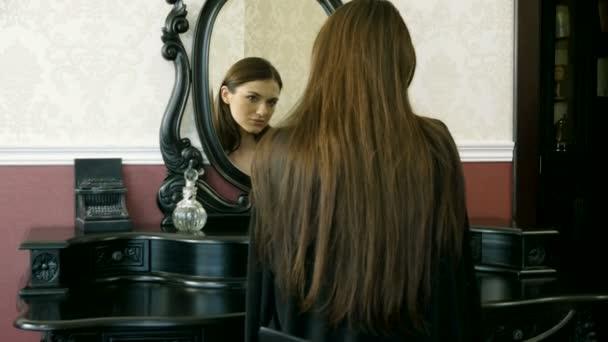 Happy usmívající se žena středního věku bruneta oblečen v černé negližé, při pohledu na svůj odraz v zrcadle doma. 4k