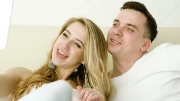 Happy couple looking at digital tablet, taking a selfie, lying in a bed at bedroom. 4K