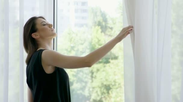 Šťastná mladá žena tahání závěsy na velké okno a díval se ven její byt na budovy ve městě. 4k