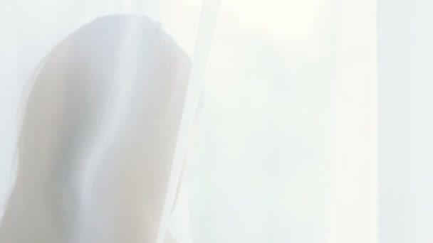 Detailní záběr krásná šťastná žena, stál jsem u okna a díval se ven zpoza záclony. 4k