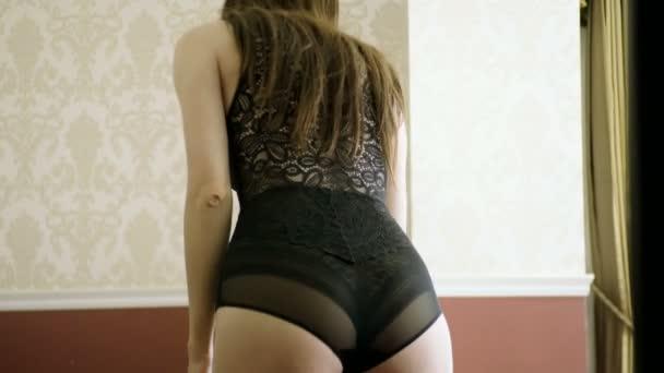 Giovane bella donna sottile indossando una vestaglia sopra la lingerie di pizzo nero in camera da letto. 4k