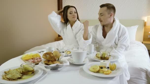 Loving couple having tasty breakfast, eating healthy food and drinking tea or coffee at luxury hotel. 4K