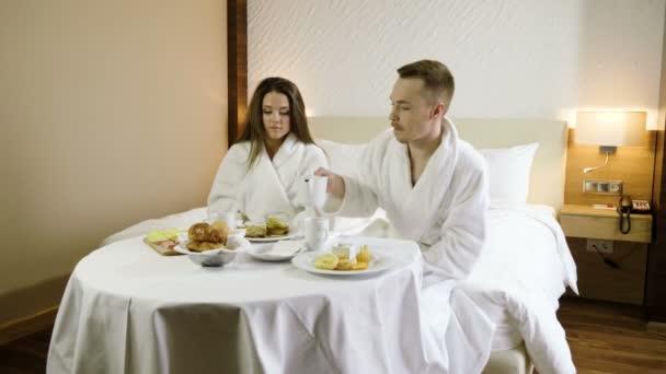 Mladí manželé oblečeni do bílých koupací róby, kteří jedí croissanty, popíjejí horký čaj, mluví a smějí se v ložnici v luxusním hotelu. 4k