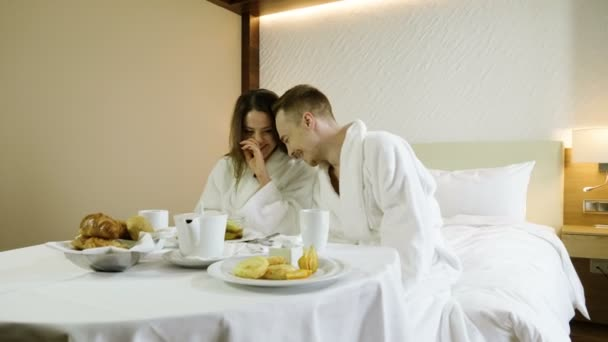 Young couple dressed in white bathrobes enjoying breakfast eating croissants, drinking hot tea, talking and laughing in bedroom at luxury hotel. 4K
