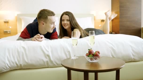 Loving couple drinking white wine, eating fresh strawberries, talking, lying on the bed in bedroom at luxury hotel. 4K