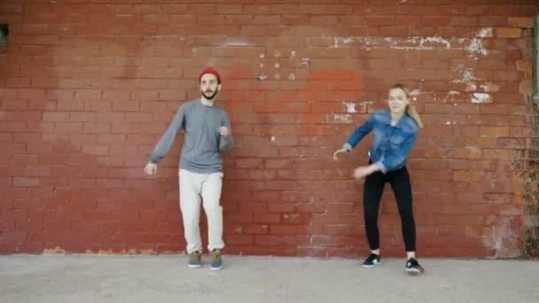 Pouliční tanec. Mladý párek profesionálních tanečníků tančí, roztančí se a provádí volný styl do tanec před červenou cihlovou stěnou. 4k