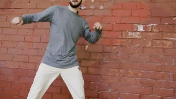 Danzatrice di strada. Giovane talentuoso uomo breakdance e di esecuzione danza Freestyle davanti a un muro di mattoni rossi. 4K