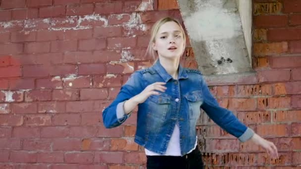 Danzatrice di strada. Giovane talentuosa donna breakdance e danza Freestyle di fronte a un muro di mattoni rossi. Rallentatore. Hd