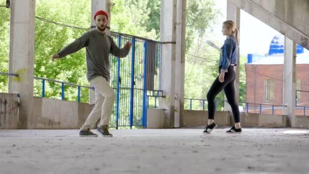 Danzatrice di strada. Giovane talentuosa donna e uomo breakdance e esecuzione di danza Freestyle. Rallentatore. Hd