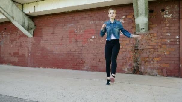Pouliční tanečnice. Mladá talentovaná žena se roztančí a provádí volný styl do tanec před červenou cihlovou stěnou. 4k