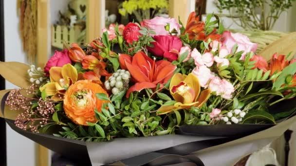 Blízkými výstřelami nádherné a stylové kytice čerstvých nejrůznějších květin v květinových návrhových ateliéru, květinářství. 4k