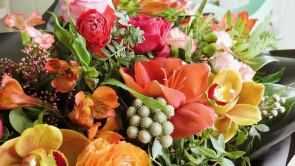 Primo piano scatto di un bellissimo ed elegante bouquet di vari fiori freschi in studio di design floreale, negozio di fiori. 4k