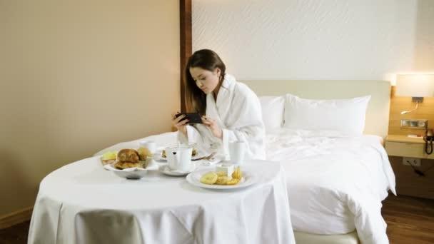 schöne junge Frau beim Fotografieren von Frühstücksessen mit dem Smartphone. 4k