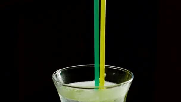 Nahaufnahme von Eis, das in ein Glas Limonade auf schwarzem Hintergrund geworfen wird. Zeitlupe. hd
