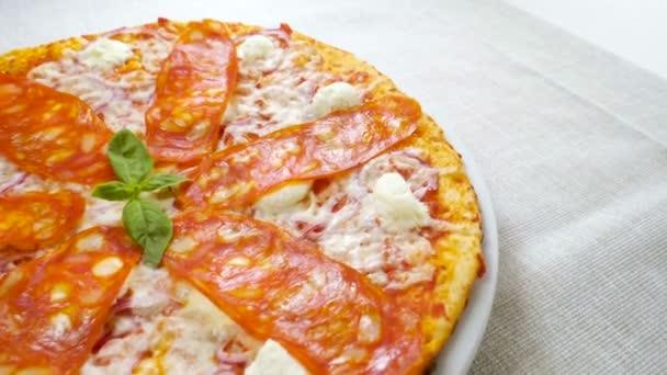Italské jídlo. Blízká střela z lahodné pizzy s rajčatovou omáčkou, salám, čerstvým bazalkovým listím, parmazánem a krémovým sýrem, červenou cibulí podávané na kulatém bílém talíři. Zpomaleně. Hd
