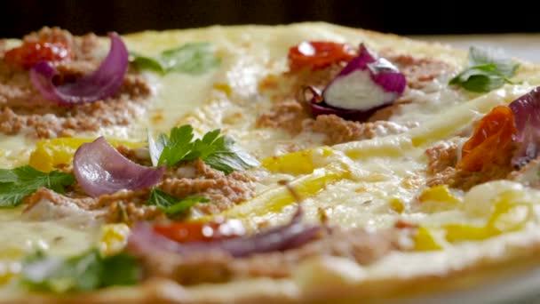 italienisches Essen. köstliche traditionelle Pizza mit Sahnesoße, frischer Petersilie, getrockneten Tomaten, roten Zwiebeln, Parmesan, Paprika, Rinderhackfleisch, Kreuzkümmel belegt. Zeitlupe. hd